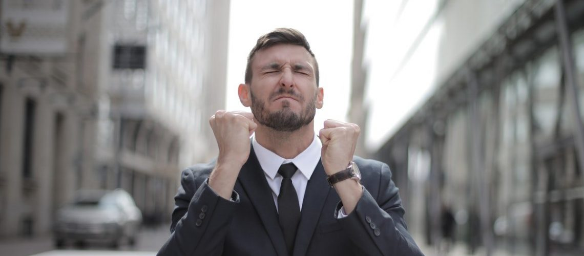 white man suit eyes closed computer fists up